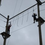 Akela leads the first Cub around the high ropes
