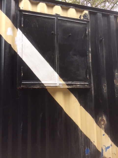 Partially painted stripe on shipping container.