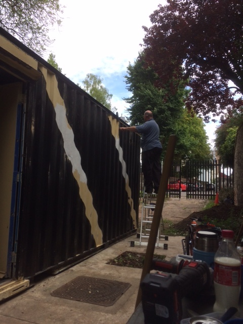 Man on ladder paints shipping container.