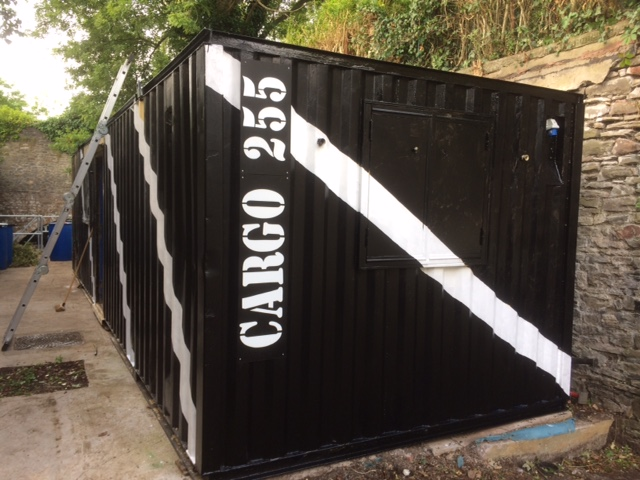 Shipping container - black with white stripes. The words CARGO 255 written  on it.